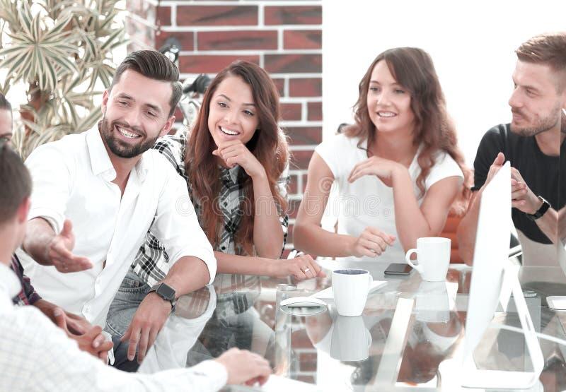 Lächelndes Team, welches die gegenwärtigen Probleme bespricht lizenzfreie stockfotos