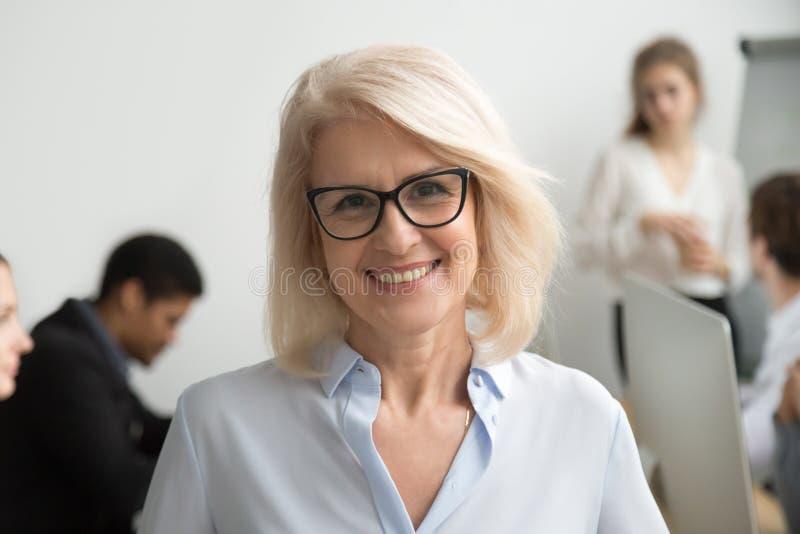 Lächelndes tragendes Glasporträt der älteren Geschäftsfrau mit busin stockfoto