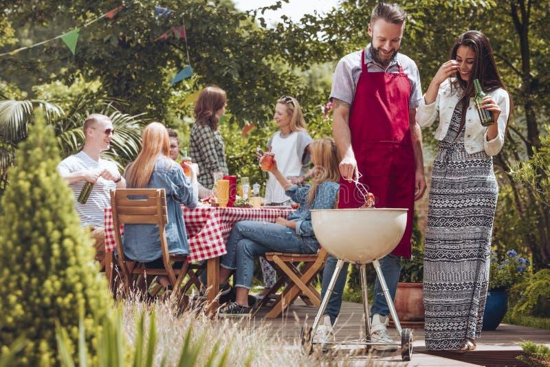 Lächelndes trinkendes Bier der Frau während ihr Freund, der Lebensmittel während Partei des Geburtstages der im Freien grillt lizenzfreies stockfoto