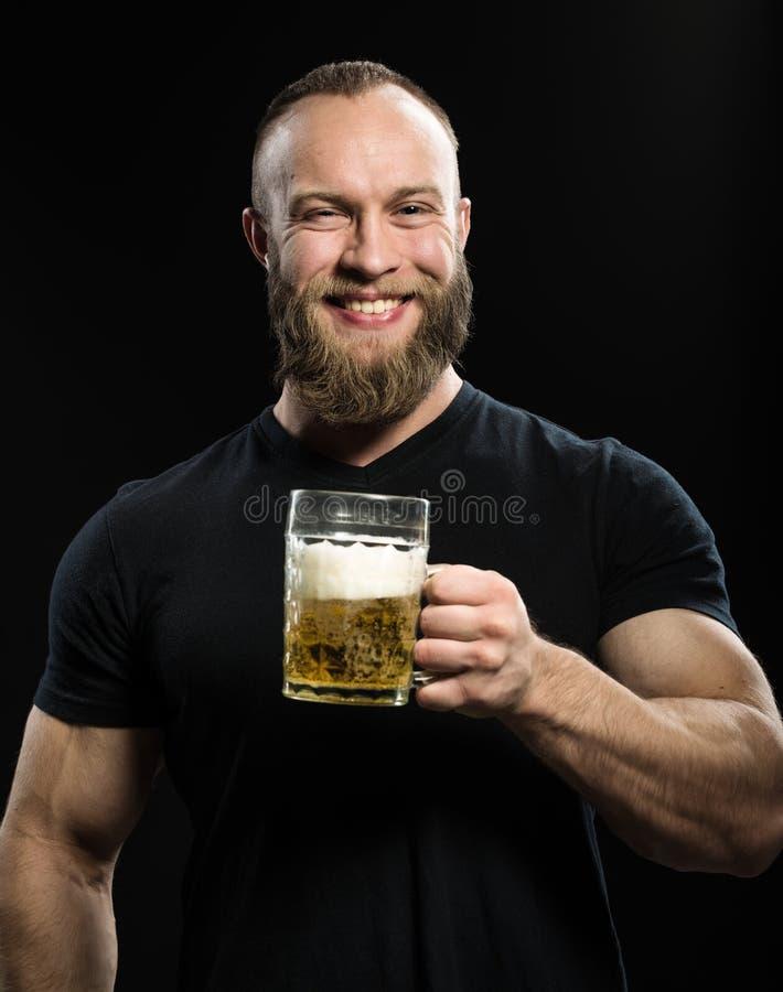 Lächelndes trinkendes Bier des bärtigen Mannes von einem Bierkrug über schwarzem BAC stockfoto