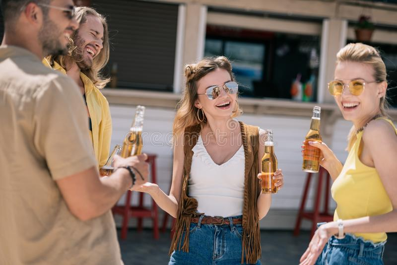 lächelndes trinkendes Bier und Unterhaltung der jungen Leute stockbilder