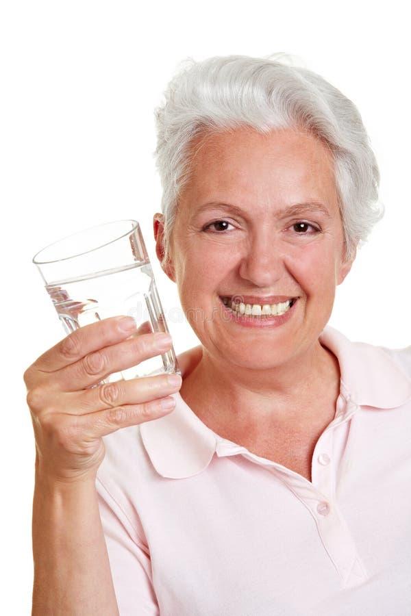 Lächelndes Trinkwasser der älteren Frau lizenzfreie stockbilder