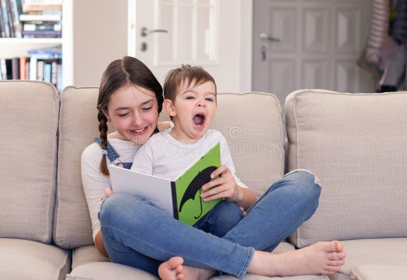 Lächelndes Tweenmädchen-Lesebuch zu ihrem netten kleinen Bruder, der auf ihrem Schoss sitzt und zu Hause auf Sofa gähnt Geschwist stockfotos