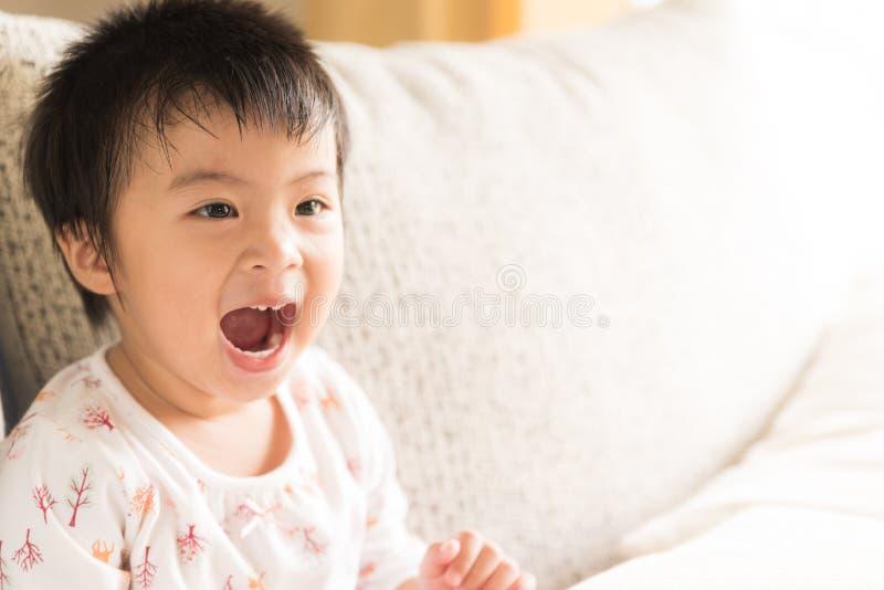 Lächelndes und lachendes Sitzen des glücklichen netten kleinen Mädchens auf Sofa lizenzfreie stockfotografie