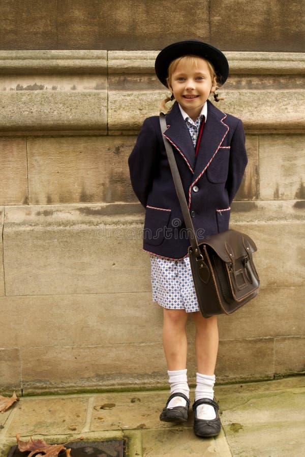 Lächelndes uniformiertes Schulmädchen, das an der Steinwand sich lehnt lizenzfreie stockbilder