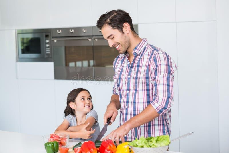 Lächelndes Vaterausschnittgemüse mit Tochter stockfotografie