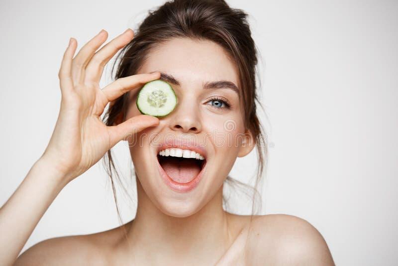 Lächelndes versteckendes Auge des jungen schönen nackten Mädchens hinter der Gurkenscheibe, die Kamera über weißem Hintergrund be lizenzfreie stockfotografie