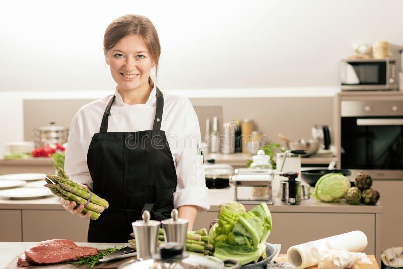 Lächelndes weibliches kitchener in der Uniform steht in der Küche im Restaurant stockfotografie