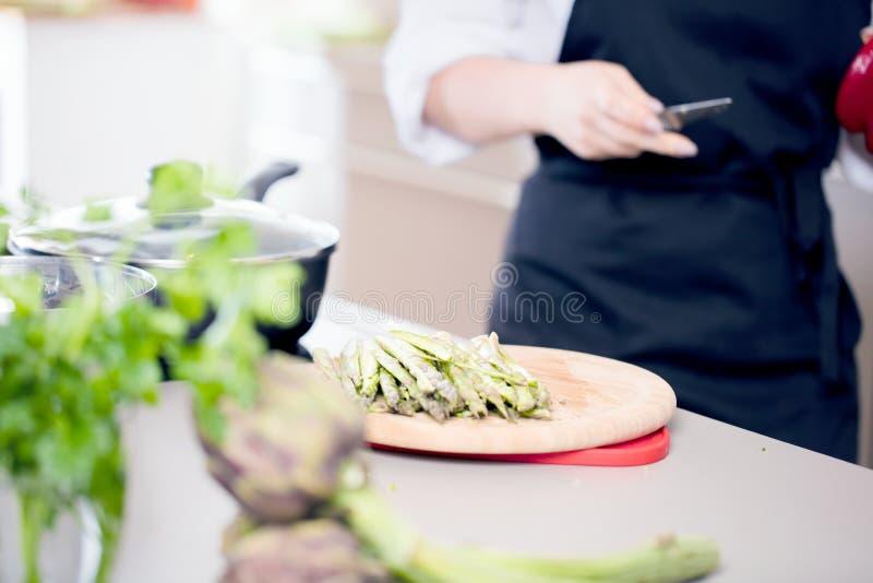 Lächelndes weibliches kitchener in der Uniform steht in der Küche im Restaurant stockfotos
