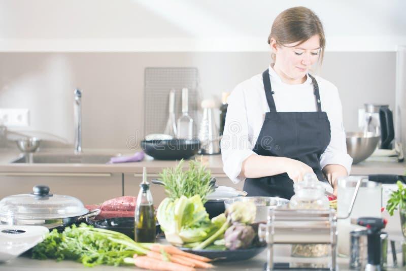 Lächelndes weibliches kitchener in der Uniform steht in der Küche im Restaurant lizenzfreie stockbilder