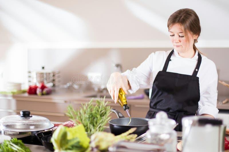 Lächelndes weibliches kitchener in der Uniform steht in der Küche im Restaurant lizenzfreie stockfotografie