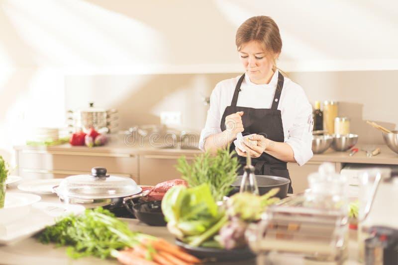 Lächelndes weibliches kitchener in der Uniform steht in der Küche im Restaurant stockbilder