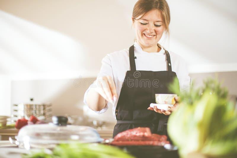 Lächelndes weibliches kitchener in der Uniform steht in der Küche im Restaurant lizenzfreies stockfoto