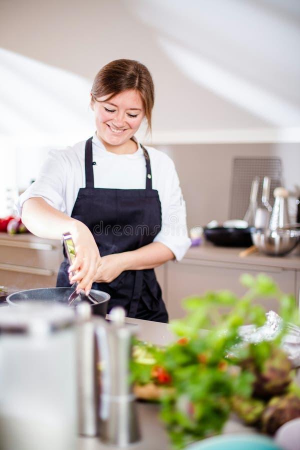 Lächelndes weibliches kitchener in der Uniform steht in der Küche im Restaurant lizenzfreie stockfotos