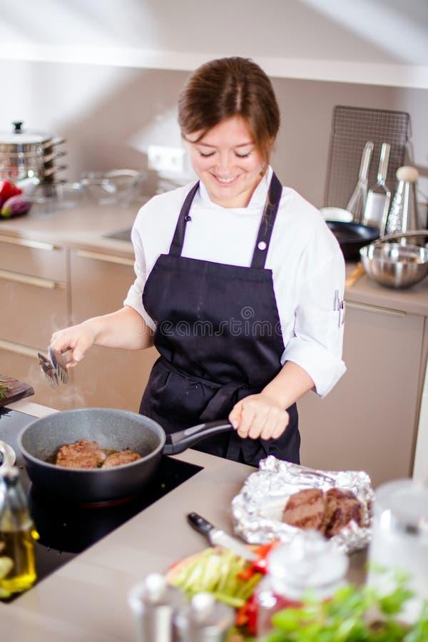 Lächelndes weibliches kitchener in der Uniform steht in der Küche im Restaurant stockbild