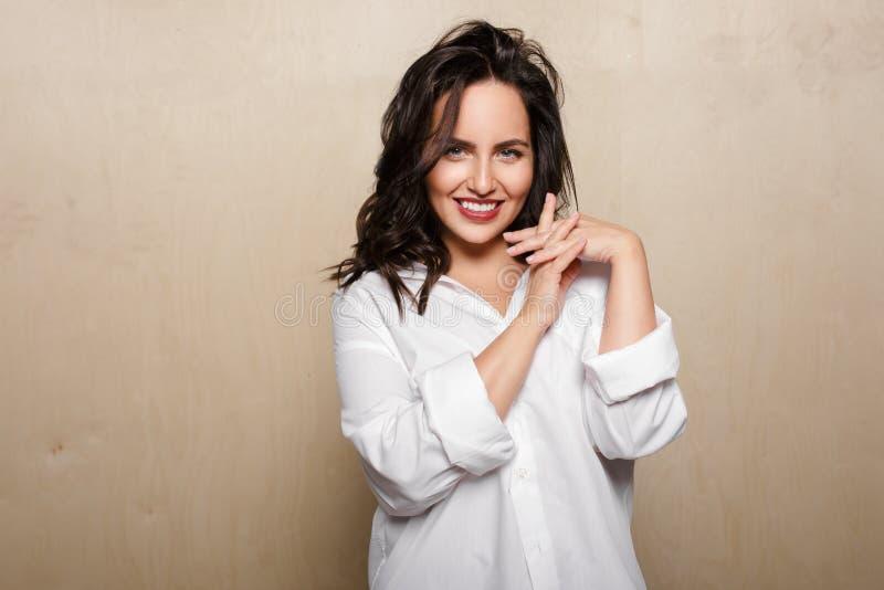 Lächelndes weibliches Modell im weißen Hemd, auf einem beige Hintergrund, gekreuzte Finger halten stockbild