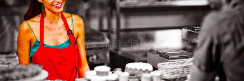 Lächelndes weibliches Personal, das zum Kunden am Zähler aufeinander einwirkt lizenzfreies stockfoto
