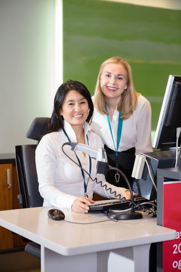 Lächelndes weibliches Personal am Flughafen-Abflugschalter lizenzfreies stockfoto