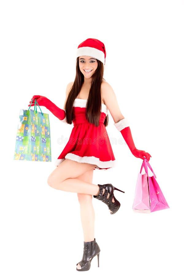 Lächelndes Weihnachtseinkaufenmädchen auf weißem Hintergrund. lizenzfreie stockbilder