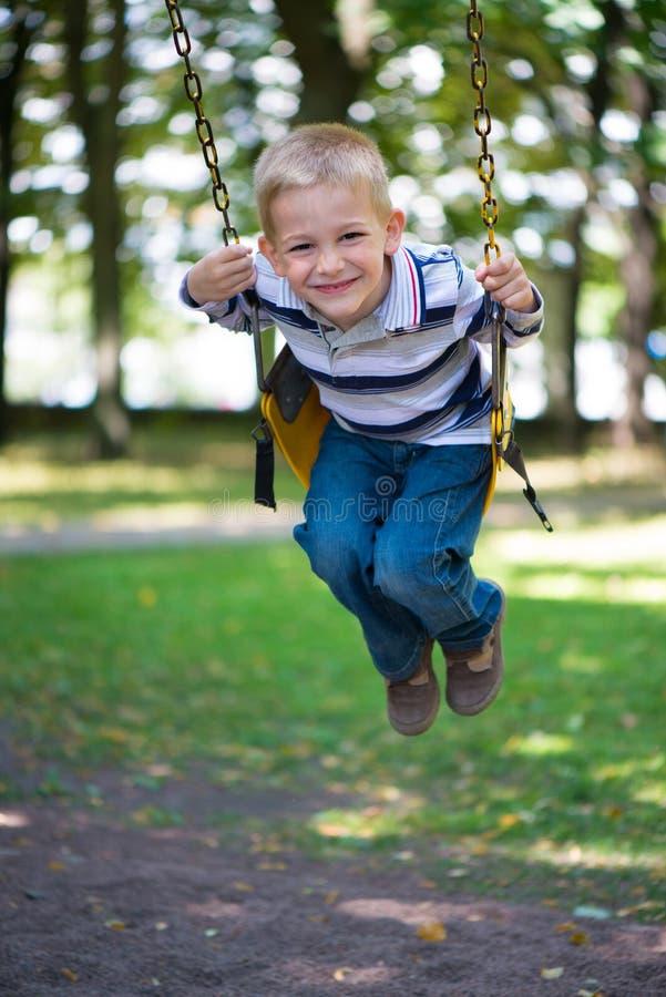 Lächelndes wenig blondes Jungenschwingen stockfotografie
