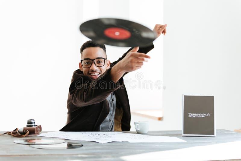 Lächelndes werfendes Vinyl des afrikanischen Mannes an der Kamera lizenzfreies stockbild