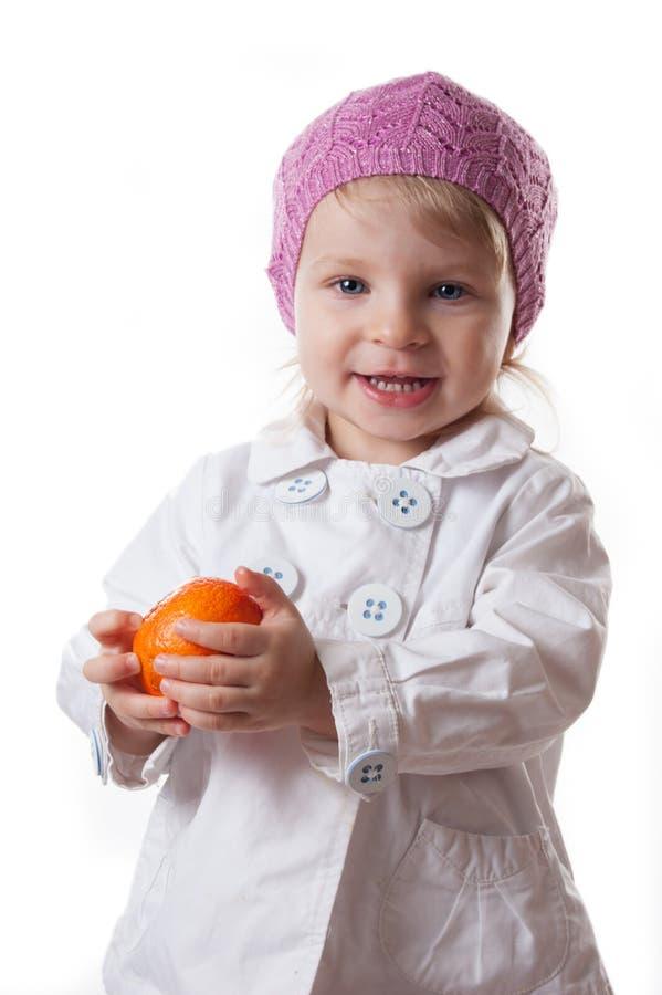Lächelndes zweijähriges Baby mit Tangerine stockfotografie