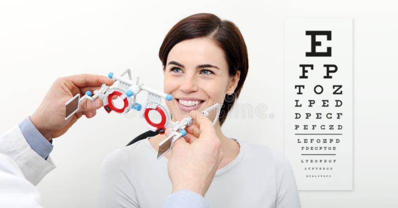 Lächelnfrau, die Sehvermögenmaß mit Proberahmen und visu tut lizenzfreie stockfotos