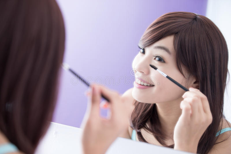 Lächelnfrau, die Wimperntuschenwimpern anwendet lizenzfreie stockfotografie