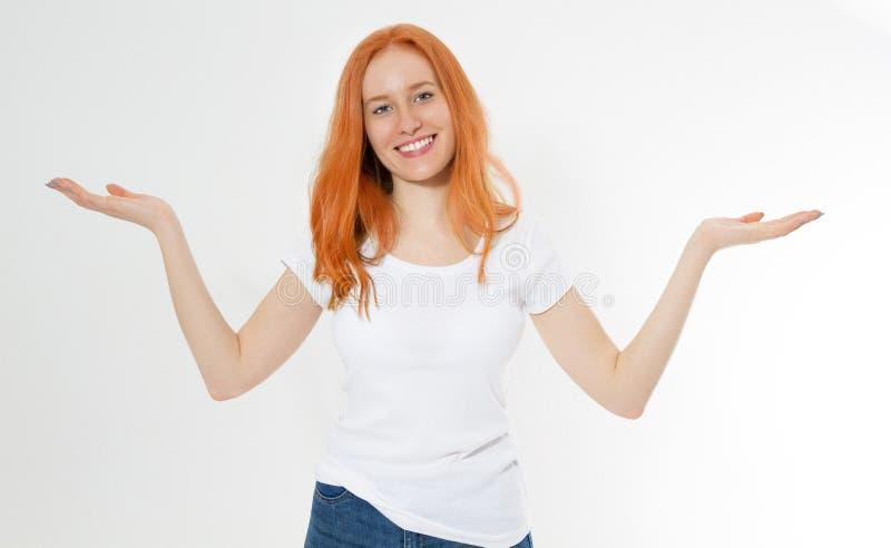 Lächelnschöne rote Hauptmädchenshowkopien-Raumhand im weißen T-Shirt lokalisiert auf weißem Hintergrund Redhair Frau zeigen - zwe stockbilder