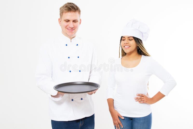 Lächelnschwarzfrau und weiße männliche Chefköche halten einen leeren Behälter lokalisiert auf weißem Hintergrund stockfotografie