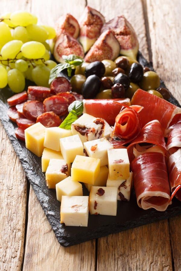 Läcker aptitretare av antipasti från ost, prosciuttoskinka, druvor, fikonträd, korvar och olivnärbild på en tabell vertikalt fotografering för bildbyråer