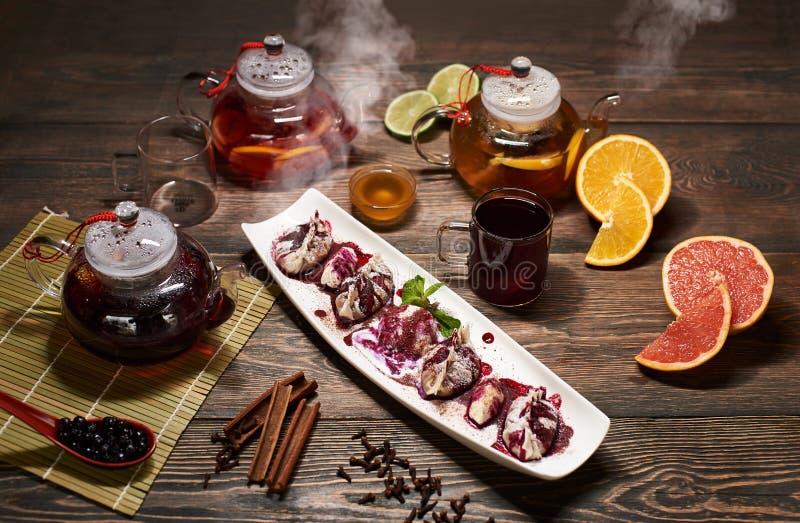 Läcker asiatisk efterrätt i den vita plattan med att ånga tekannor, frukter, bär och kryddor Asiatisk meny spelrum med lampa arkivbild