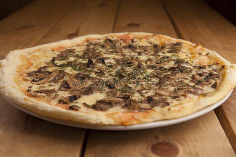 Läcker champinjonpizza på en trätabell arkivfoto