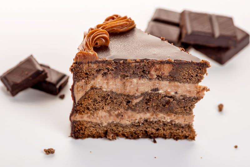 Läcker chokladkaka med choklad som är bruten på vit fotografering för bildbyråer