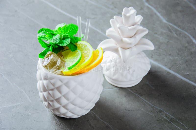 Läcker exotisk coctail i ett exponeringsglas i form av ananas arkivbilder