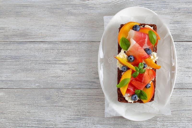 Läcker färgrik öppen smörgås med skinka royaltyfria foton