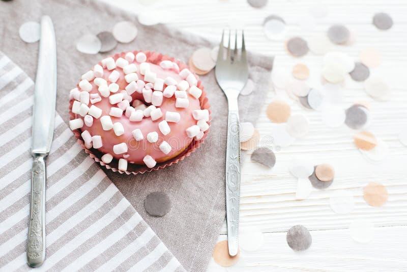 Läcker färgrik rosa munk med stänk och marshmallower på den stilfulla vita tabellen med konfettier och gaffel och kniv deltagare royaltyfri fotografi