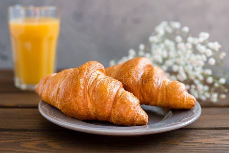 Läcker frukost med giffel, blommor och fruktsaft, bra morgon Exponeringsglas av förnyelse av orange fruktfruktsaft arkivfoton