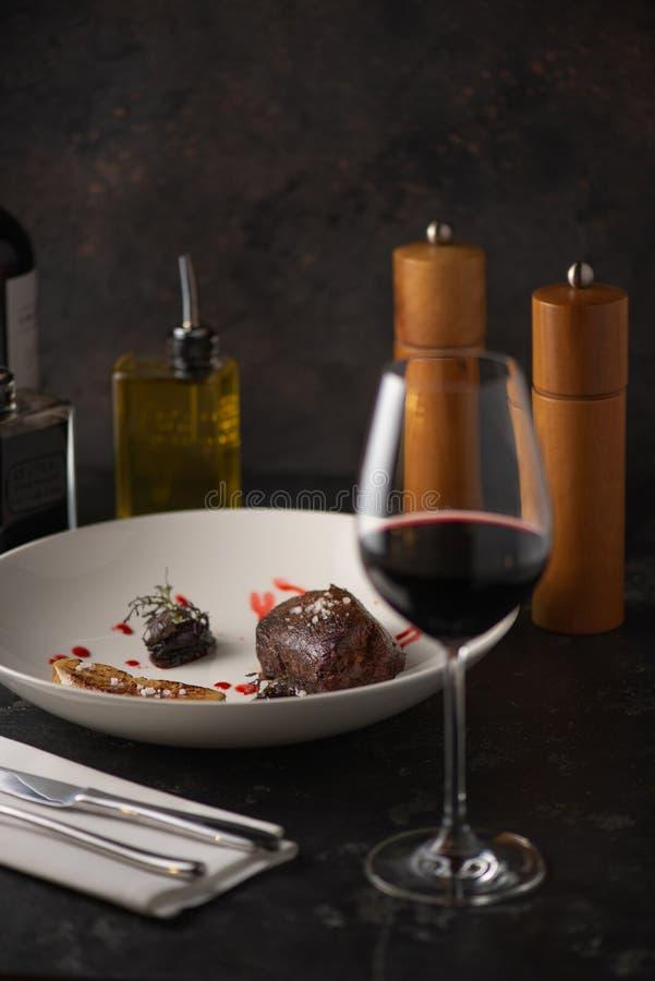 Läcker grillad biff med ett vinexponeringsglas Restaurang royaltyfri bild