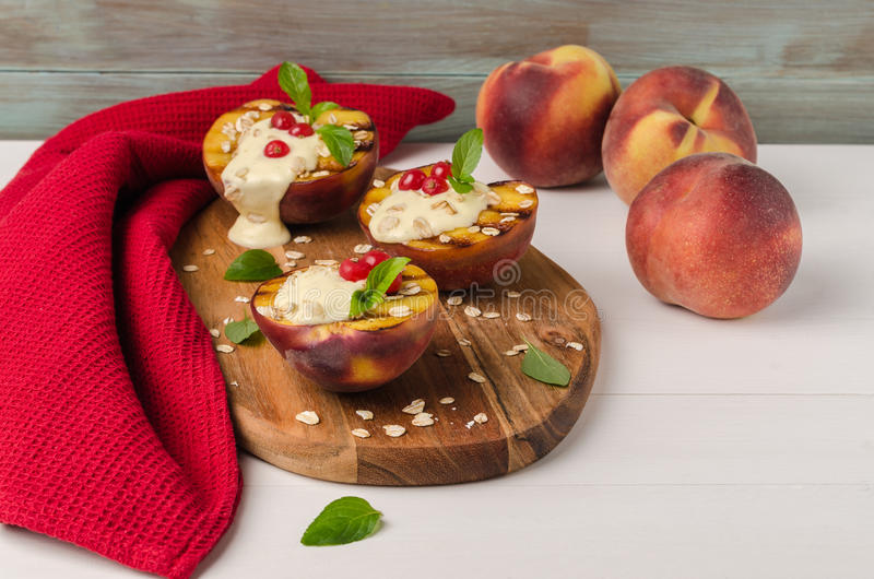 Läcker grillad persikaefterrätt med yoghurten, krusbär och arkivbilder