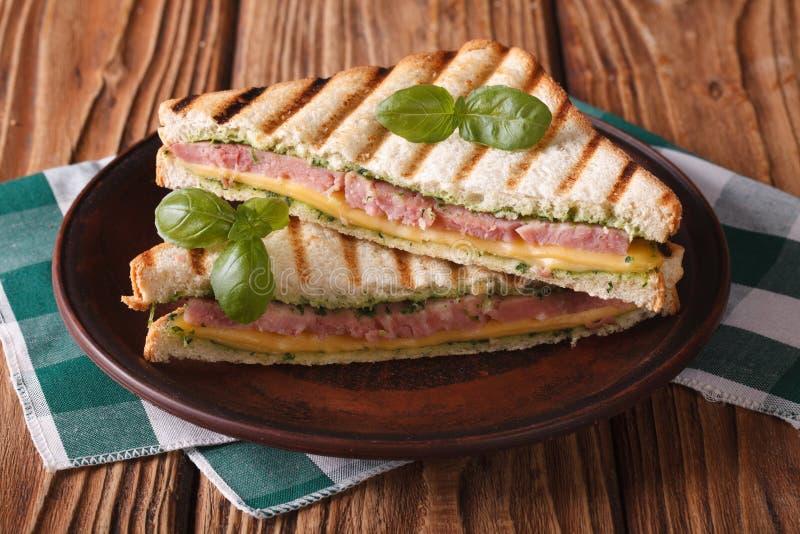 Läcker grillad smörgås med skinka, ost och basilika royaltyfri foto