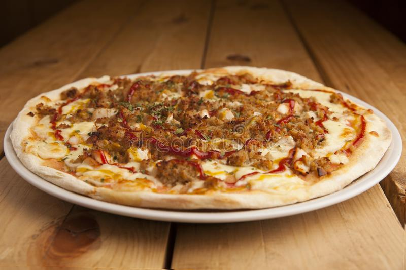 Läcker grillfestpizza på en trätabell royaltyfri fotografi