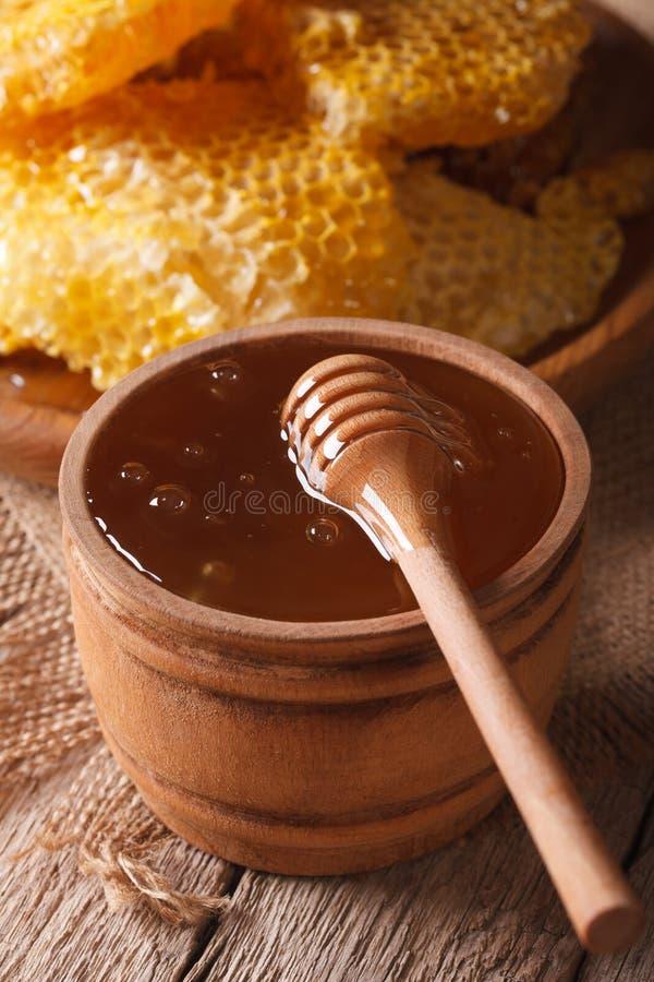 Läcker guld- honung i en träbunke med en pinne royaltyfri foto