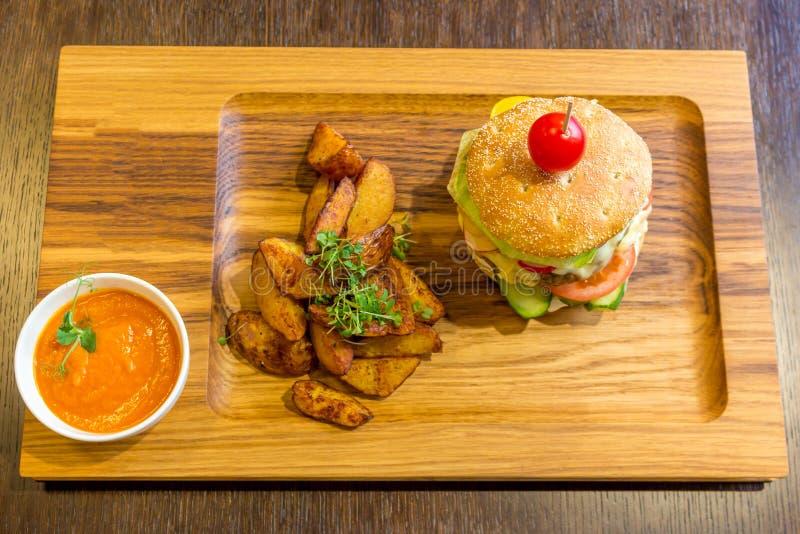 Läcker hamburgare med kött, grönsaker, potatisar och orange sauc arkivbilder