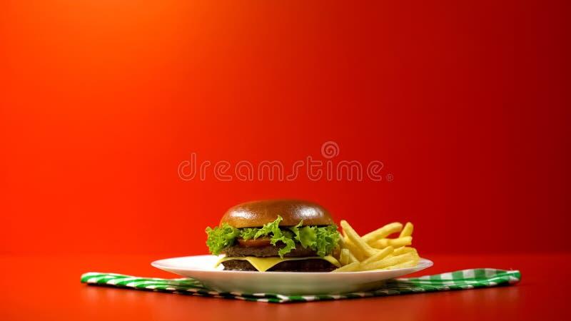 Läcker hamburgare som tjänas som med franska småfiskar i kafét, platta på rutig servett royaltyfri foto