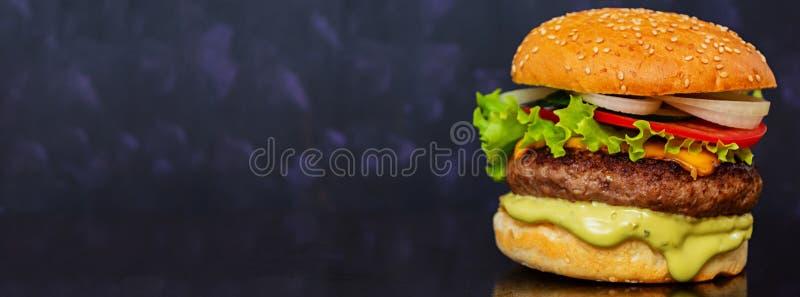 Läcker handgjord hamburgare på mörk bakgrund baner arkivbilder