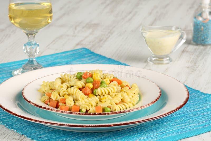 Läcker hemlagad fusillipasta som lagades mat med basilikapesto, morötter, havre och ärtor i en platta på en turkosblåttservett, t royaltyfri fotografi