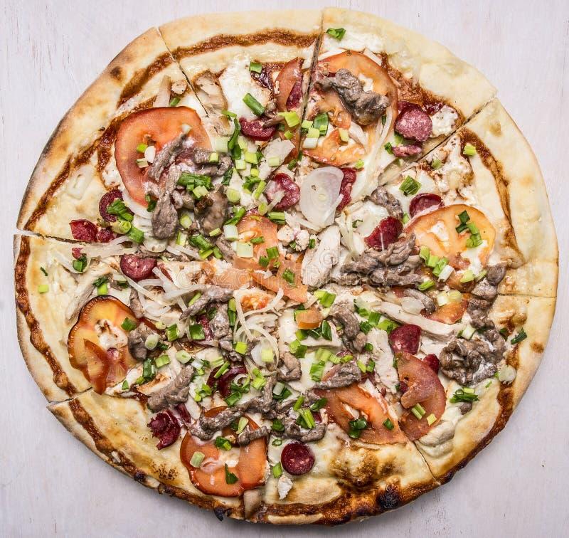 Läcker hemlagad pizza med slut för bästa sikt för tomat-, korv-, lök-, höna- och ostträlantligt bakgrund upp royaltyfria foton