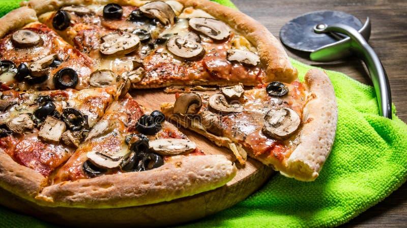 Läcker italiensk pizza på tyget trägrund tabell för djupfält arkivfoton