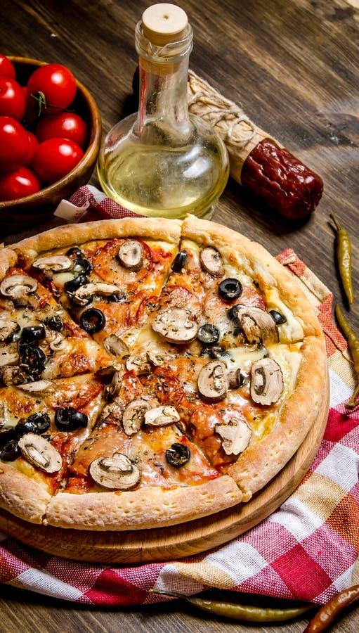 Läcker italiensk pizza på tyget trägrund tabell för djupfält arkivbild